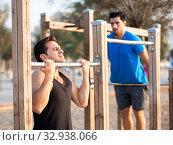 Купить «Smiling adult men are doing pull-ups», фото № 32938066, снято 6 сентября 2017 г. (c) Яков Филимонов / Фотобанк Лори