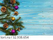 Купить «Зеленые ветви пихты, сосновые шишки и новогодние шары  на краю синего деревянного стола», фото № 32938654, снято 8 января 2020 г. (c) Наталья Гармашева / Фотобанк Лори
