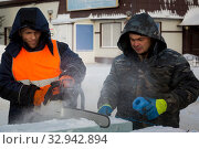 Worker cuts ice panel with gasoline saw (2019 год). Редакционное фото, фотограф Андрей Кузнецов / Фотобанк Лори