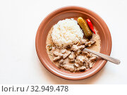 Russian cuisine dish - eating of Beef Stroganoff (Beef Stroganov, Befstroganov) pieces of stewed meat in sour cream with boiled rice on brown plate on white board. Стоковое фото, фотограф Zoonar.com/Valery Voennyy / easy Fotostock / Фотобанк Лори