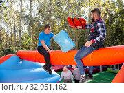 Купить «Men having funny battle at amusement park», фото № 32951162, снято 18 февраля 2020 г. (c) Яков Филимонов / Фотобанк Лори