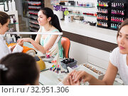 Купить «Manicurists giving manicure to female clients at nail salon», фото № 32951306, снято 28 апреля 2017 г. (c) Яков Филимонов / Фотобанк Лори