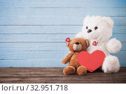 Купить «Teddy bear with red heart on old wooden background. Valentine's», фото № 32951718, снято 14 декабря 2019 г. (c) Майя Крученкова / Фотобанк Лори