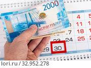 Купить «Hand holds wad of money over calendar number 30», фото № 32952278, снято 16 января 2020 г. (c) Иванов Алексей / Фотобанк Лори