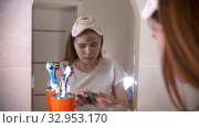 A young woman applying a face mask on her face using a brush. Стоковое видео, видеограф Константин Шишкин / Фотобанк Лори
