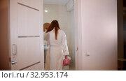 Купить «A young woman walking in the bathroom in her bathrobe», видеоролик № 32953174, снято 5 июня 2020 г. (c) Константин Шишкин / Фотобанк Лори