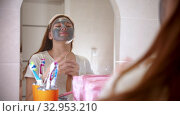 A young attractive woman with a mask on her face dancing and singing in front of the mirror in bathroom. Стоковое видео, видеограф Константин Шишкин / Фотобанк Лори