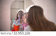 A young pretty woman washes off the mask from the face. Стоковое видео, видеограф Константин Шишкин / Фотобанк Лори