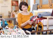 Купить «Brunette choosing fabric in store», фото № 32953554, снято 7 февраля 2019 г. (c) Яков Филимонов / Фотобанк Лори
