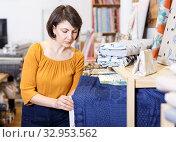Купить «Woman looking for cloth in shop», фото № 32953562, снято 7 февраля 2019 г. (c) Яков Филимонов / Фотобанк Лори