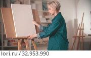 Купить «A young woman artist putting a clear canvas on the easel», видеоролик № 32953990, снято 25 февраля 2020 г. (c) Константин Шишкин / Фотобанк Лори