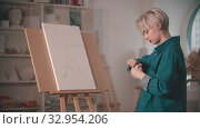 A young woman artist opening up a beige paint to color her painting. Стоковое видео, видеограф Константин Шишкин / Фотобанк Лори