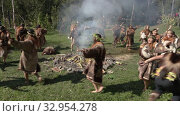 Group Itelmens people dancing ritual dance near fire and scream in traditional clothing aboriginal. Itelmens national ritual festival thanksgiving nature Alhalalalay. Kamchatka Peninsula (2019 год). Редакционное видео, видеограф А. А. Пирагис / Фотобанк Лори