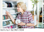 portrait of female customer standing next to different bands for sewing in shop. Стоковое фото, фотограф Яков Филимонов / Фотобанк Лори