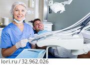 Купить «Female dentist with male patient in chair», фото № 32962026, снято 5 июля 2017 г. (c) Яков Филимонов / Фотобанк Лори
