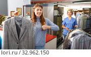 Купить «Portrait of cheerful female laundry customer holding clean clothes on hanger», фото № 32962150, снято 22 января 2019 г. (c) Яков Филимонов / Фотобанк Лори