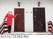 Double door entrance of townhouse with high porch and woman showing hand for choise. Стоковое фото, фотограф Кекяляйнен Андрей / Фотобанк Лори