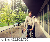 Купить «young man riding bicycle on city street», фото № 32962750, снято 21 августа 2016 г. (c) Syda Productions / Фотобанк Лори