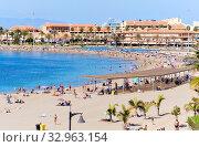 Tenerife, Spain - October 13, 2019: People sunbathing on sandy beach of Playa de los Cristianos, enjoy warm Atlantic Ocean waters, townscape and hotels exterior, Tenerife, Canary Islands, Spain. Редакционное фото, фотограф Alexander Tihonovs / Фотобанк Лори