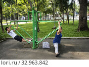 Two people exercise early in the morning in a park in Ho Chi Minh (Vietnam) is very popular vesta custom among the Vietnamese. HO CHI MINH- VIETNAM. (2017 год). Редакционное фото, фотограф Joaquín Gómez / age Fotostock / Фотобанк Лори
