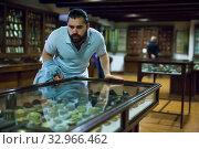 Attentive adult man exploring artworks in glass case in museum. Стоковое фото, фотограф Яков Филимонов / Фотобанк Лори