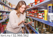 Купить «Female in the shop choosing preserved fish», фото № 32966562, снято 11 апреля 2018 г. (c) Яков Филимонов / Фотобанк Лори