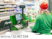 Russia, Samara, December 2019: Cashier of a supermarket. A girl in a green uniform and a Christmas hat is standing at the checkout. Text in Russian: chocolate bar, subtotal, payment, use a pin pad. Редакционное фото, фотограф Акиньшин Владимир / Фотобанк Лори