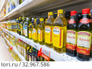 Купить «Russia Samara December 2019: Shelves with sunflower oil in a supermarket. Text in Russian: olive oil, discount, a touch of the Mediterranean», фото № 32967586, снято 25 декабря 2019 г. (c) Акиньшин Владимир / Фотобанк Лори
