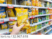 Купить «Russia Samara December 2019: A hand holds a package with chips on the background of a rack with chips in a supermarket. Text in Russian: discount, classic», фото № 32967618, снято 25 декабря 2019 г. (c) Акиньшин Владимир / Фотобанк Лори
