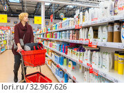 Russia Samara November 2019: a woman chooses shampoo in a store in the department of perfumes and cosmetics. Text in Russian: discount, exit. Редакционное фото, фотограф Акиньшин Владимир / Фотобанк Лори