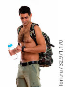 Купить «Studio shot of young muscular Persian man holding water bottle while looking at his watch and checking time shirtless», фото № 32971170, снято 26 января 2020 г. (c) easy Fotostock / Фотобанк Лори