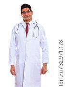 Купить «Studio shot of young muscular Persian man doctor standing isolated against white background», фото № 32971178, снято 25 января 2020 г. (c) easy Fotostock / Фотобанк Лори