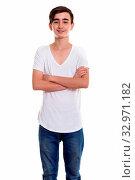 Купить «Studio shot of young happy Persian teenage boy smiling and standing with arms crossed», фото № 32971182, снято 26 января 2020 г. (c) easy Fotostock / Фотобанк Лори