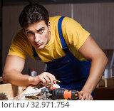 Купить «The worker working in repair workshop in woodworking concept», фото № 32971754, снято 11 августа 2017 г. (c) Elnur / Фотобанк Лори