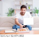 Купить «Man eating pizza having a takeaway at home relaxing resting», фото № 32971802, снято 18 июля 2017 г. (c) Elnur / Фотобанк Лори