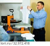Купить «Man using a serigraph press to print a shirt in a workshop», фото № 32972418, снято 3 августа 2020 г. (c) Яков Филимонов / Фотобанк Лори