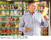 Купить «Man choosing vegetable seeds», фото № 32972518, снято 9 октября 2019 г. (c) Яков Филимонов / Фотобанк Лори
