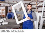 Купить «Laborer is demonstrating the window frame», фото № 32972530, снято 30 марта 2017 г. (c) Яков Филимонов / Фотобанк Лори