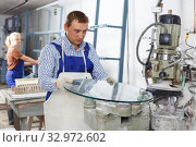 Купить «Craftsman working on machine for curved glass faceting», фото № 32972602, снято 10 сентября 2018 г. (c) Яков Филимонов / Фотобанк Лори