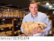 Купить «Portrait of adult man buying pasta», фото № 32972674, снято 9 октября 2019 г. (c) Яков Филимонов / Фотобанк Лори