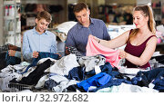 Купить «Mother,father and son choosing wear at the clearance sale shop», фото № 32972682, снято 13 апреля 2017 г. (c) Яков Филимонов / Фотобанк Лори