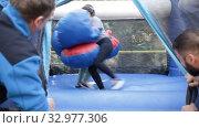 Купить «Cheerful women in big boxing gloves boxing on inflatable ring in outdoor amusement park», видеоролик № 32977306, снято 12 ноября 2019 г. (c) Яков Филимонов / Фотобанк Лори