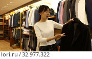 Polite young Chinese salesgirl offering stylish suit coats in men clothing store. Стоковое видео, видеограф Яков Филимонов / Фотобанк Лори