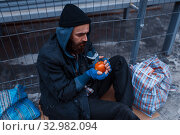 Male person gives food to bearded dirty beggar. Стоковое фото, фотограф Tryapitsyn Sergiy / Фотобанк Лори