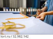 Купить «Seamstress cuts fabric with scissors in store», фото № 32982142, снято 8 ноября 2019 г. (c) Tryapitsyn Sergiy / Фотобанк Лори