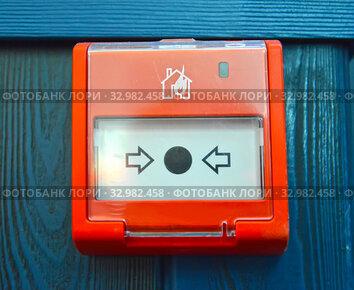 Кнопка пожарной сигнализации на синей деревянной стене помещения