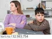 Upset mother and unhappy son sitting after quarrel indoors. Стоковое фото, фотограф Яков Филимонов / Фотобанк Лори