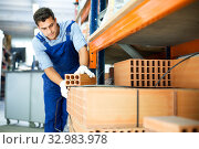 Купить «Shop assistant man is checking quality of bricks», фото № 32983978, снято 26 июля 2017 г. (c) Яков Филимонов / Фотобанк Лори