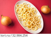 Купить «Chips onion rings in a white plate and onions on a red background», фото № 32984254, снято 10 августа 2019 г. (c) Катерина Белякина / Фотобанк Лори