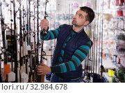 Fisherman consumer choosing fishing rod in shop. Стоковое фото, фотограф Яков Филимонов / Фотобанк Лори